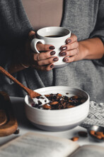 A Young Woman Drinks Morning Coffee, Eats A Healthy Breakfast And Reads A Book. Morning Routine. Stylish Manicure. Correct Habits. Holding A Cup In His Hands
