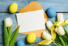 Easter Holiday Greeting Card Mockup Over Old Blue Wooden Background With Colored Eggs
