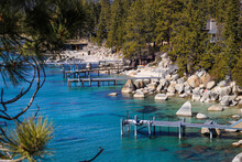 A Stunning Shot Of The Deep Blue Lake Water With Wooden Boat Docks On The Lake And Lush Green Pine Trees And Rocks On The Banks Of The Lake And Snow Capped Mountains At Lake Tahoe Nevada State Park