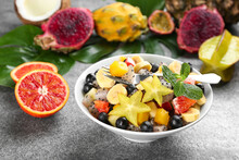 Delicious Exotic Fruit Salad And Ingredients On Grey Table