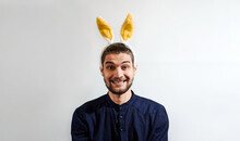 Man With Rabbit Ears. Charming Young Man With Beard In Shirt Wearing Easter Bunny Costume. Persom With Hare Ears Smiles Big Smile. Creative Banner For Celebration Of Easter.