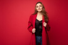 Young Beautiful European Stylish Brunette Woman Wearing Black Blouse Top And Red Cardigan Isolated Over Red Background With Positive Sincere Emotions. Simple And Natural Looking At The Camera. Free