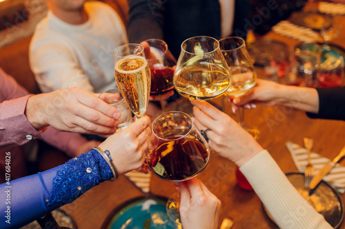 Fotografiet Clinking glasses with alcohol and toasting, party.