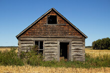 The Front Of An Abandoned Gray Weathered Log Cabin In Good Shape In A Field In A Countryside Landscape