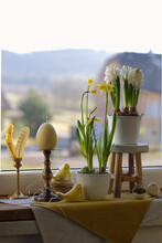 Daffodils And Hyacinths In Flower Pots On The Windowsill. Easter Home Decoration On A Blurry Background. Egg-candle In A Copper Candlestick