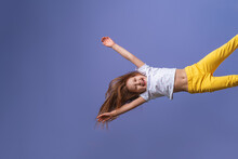 Crazy Excited Little Fun Girl Hanging Happy Upside Down Hands Up On Isolated Purple Studio Background. Dynamic Children's Image. Emotions, Expression. Copy Space