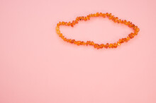 Closeup Shot Of An Amber Beads Necklace On A Pink Surface