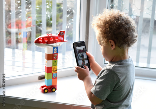 Photo 3 year old boy using cell phone to take pictures of his Lego creation