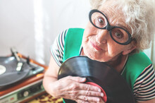 Elderly Pretty Woman With Glasses Listens To Vinyl Records On A Turntable. Retro Music. Grandma Is Nostalgic Listening To Music. Entertainment For Pensioners. Retro Style. Hipster Grandma. Nostalgia