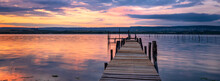 Amazing Mood Sunset At A Lake Coast With A Boat At A Wooden Pier. Panoramic View