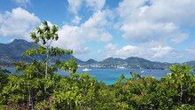 View Over Green Trees To Mahe Island With The Capital Victoria And Green Hills, Blue Turquoise Sea In Between, Blue Sky And White Clouds