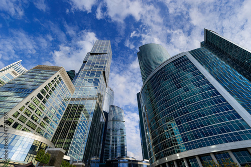 Skyscrapers, modern business office buildings in commercial district, architecture raising to the blue sky with white clouds, bottom view
