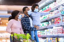 Shopping During Covid-19 Outbreak. Young Black Family Wearing Disposable Masks While Buying Dairy Products At Mall