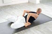 Rear View On Yogi Male Exercising, Doing Mandukasana - Frog Pose On Fitness Mat, Flexible Sportive Man Stretching Body. Alone In Bright Studio Class