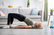 Stay at home fitness. Strong mature woman doing half bridge yoga pose, strengthening her abs muscles indoors, copy space