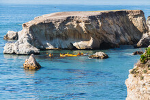 Ocean Kayaking. Group Of People Paddling Kayaks Overlooking Pacific Ocean, Rocky Cliffs And Caves Close To Shell Beach, California Coastline