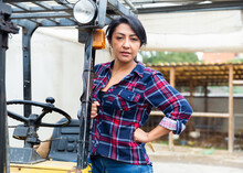 Hispanic Woman Working At The Company Gets Behind The Wheel Of A Forklift Truck ...