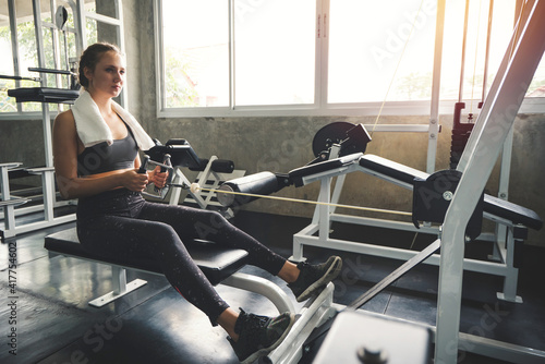 Young woman lowering weight of fitness machine and working out in the fitness gym © weerayut
