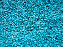 The Wall Of The Building Is Decorated With Fine Gravel And Painted Blue. Abstract Background With Plaster And Pebbles.