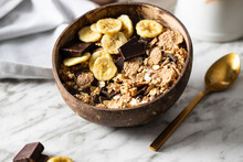 Close Up Of Muesli  In Coconut Bowl With  Banana And Chocolate On The Marble Table. Mix Of Unprocessed Whole Grains, Chia, Quinoa, Nuts, Seeds, Fruit For Heathy Breakfast.