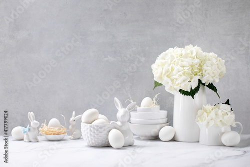 Obraz Easter decorations such as porcelain bunnies and eggs on a kitchen countertop - fototapety do salonu