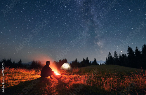 Fotografia Silhouette of male traveler sitting near campfire under night sky with stars and Milky way