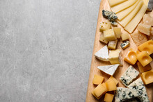 Cheese Plate On Grey Table, Top View. Space For Text