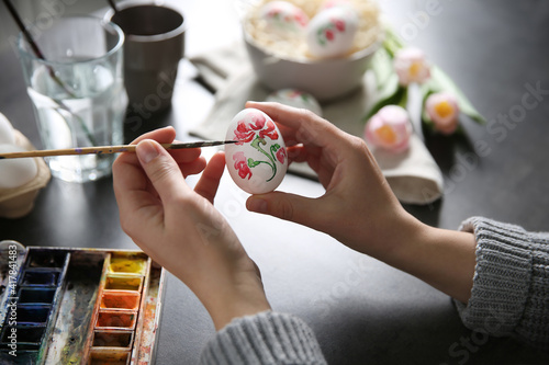 Obraz Woman painting Easter egg at black table, closeup - fototapety do salonu