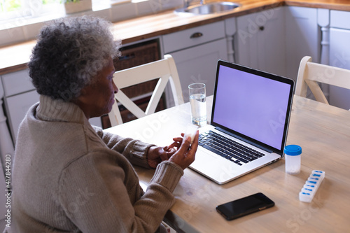 African american senior woman holding empty medication container while having a videocall on laptop