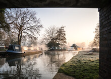 Stunning Old Canal House Boats Landscape Under Bridge Sunrise In Countryside With River And Single Lone Wooden Bench. Frost On Grass Reflection Of Trees And Vessels Chimney Smoke In Still Calm Water