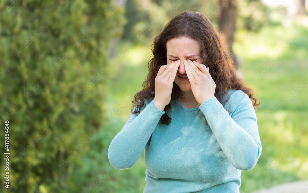 Fototapeta Woman suffering itching scratching eyes outdoors in a park