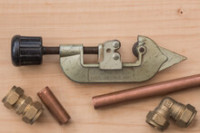 Pipe Cutter With Copper Pipe And Compression Fittings. Wooden Background With Close Up View From Above.