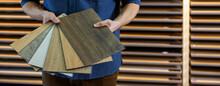 Flooring Store Seller With Vinyl Floor Samples In Hands. Copy Space