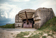 Atlantic Wall Concrete German World War Two Gun Emplacement Fortification Bunker Naval Battery At Longues-sur-mer In Normandy Gold Beach France Remains Lay In Ruins With Dramatic Cloudy Storm Sky