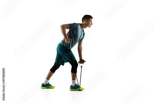 Fototapeta Work out. Young caucasian male model in action, motion isolated on white background with copyspace. Concept of sport, movement, energy and dynamic, healthy lifestyle. Training, practicing. Authentic. obraz