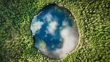 An Almost Perfect Circular Lake Shot Straight Down From The Air Resembles The Earth Surrounded By A Pine Forest