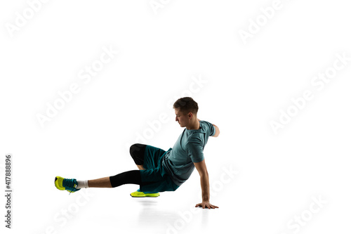 Fototapeta Stretching. Young caucasian male model in action, motion isolated on white background with copyspace. Concept of sport, movement, energy and dynamic, healthy lifestyle. Training, practicing. Authentic obraz