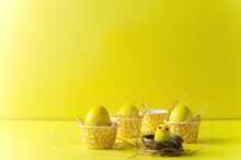Bright, Yellow Easter Eggs In Yellow Confectionery Capsules Stand On A Yellow Background. Ahead Is A Little Decorative Chicken In The Nest, Copying The Space, Selective Focus