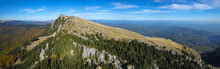 Aerial Panorama Of Buila Massif With Its Rocky Crest. The Mountain Has Sharp Abysses Covered With Beech And Spruce Forests. Sunny Autumn Day With A Blue Sky. Carpathia, Romania.