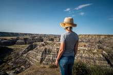Female Traveler Looking At View At Horseshoe Canyon Near Drumheller In Alberta, Canada.