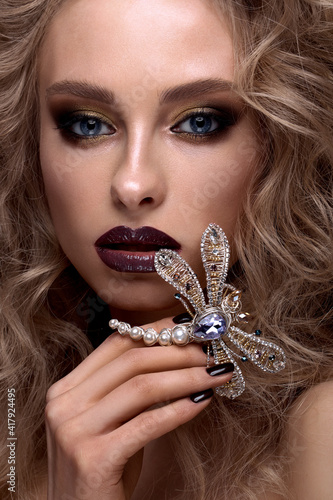 Foto Beautiful blonde girl with curls, bright make-up and designer accessories