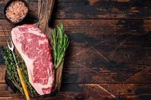 Raw New York Strip Beef Steak Or Striploin On A Wooden Board. Dark Wooden Background. Top View. Copy Space