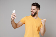 Young Bearded Caucasian Man 20s Wear Casual Yellow Basic T-shirt Do Selfie Shot On Mobile Phone Do Winner Gesture Clench Fist Talking By Video Call Isolated On Grey Color Background Studio Portrait