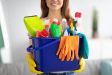 Unrecognizable Millennial Maid Holding Bucket With Cleaning Supplies Indoors, Closeup Of Hands. Sanitary Service Concept