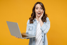 Young Happy Surprised Shocked Brunette Fun Woman 20s Wearing Stylish Casual Denim Shirt White T-shirt Hold Laptop Pc Computer Hold Face Look Camera Isolated On Yellow Color Background Studio Portrait