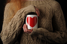 A White Mug With A Red Heart In The Hands Of A Girl In A Knitted Sweater