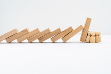 Group Of Wooden Peg Dolls Resisting And Stopping Domino Effect Falls.