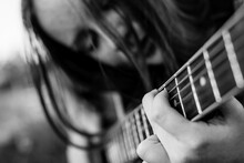 Girl Playing Acoustic Guitar – Fingers On The Strings. Black And White Photo.