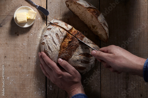Foto Close up of man cutting homemade sourdough bread loaf on wood table