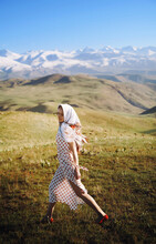Beautiful Woman With Headscarf Walking On Grass Against Clear Blue Sky